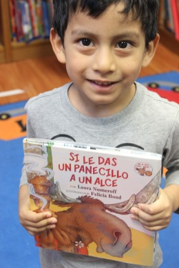 child in library and Spanish book